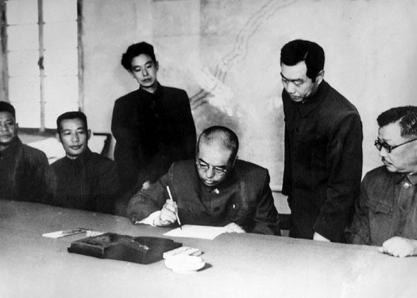 中国人民志愿军司令员兼政治委员彭德怀在停战协定上签字(资料图)