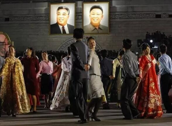 2012年4月,朝鲜民众在金日成和金正日画像下起舞庆祝金日成生日。