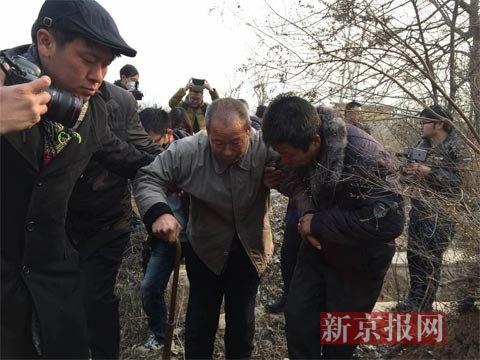 聂树斌父亲聂学生在众人搀扶下来到聂树斌坟前。