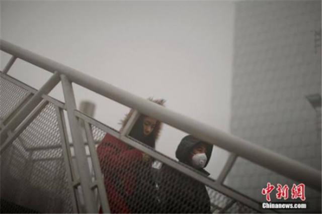 12月4日,戴着口罩的行人从天桥上走过。天津市气候台当日7时公布大雾橙色预警信号,天津大有些地区覆盖在大雾中,部分地域能见度低于200米。