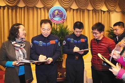 12月7日,航天员景海鹏(左二)、陈冬(左三)在与媒体见面时为记者签名。 新华社记者 琚振华 摄