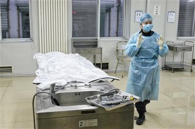 一名女法医在剖解台阁下预备工作。本版拍照/新京报记者 王嘉宁