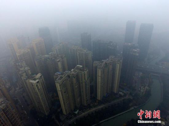 12月8日,成都市区的高楼笼罩在雾霾中。中新社记者 张浪 摄