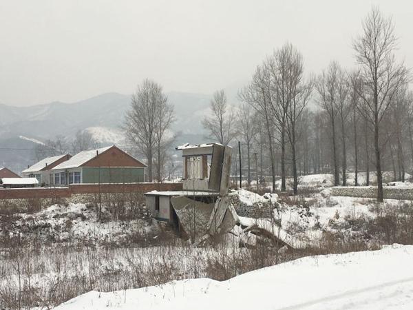 """经岫岩县偏岭镇通往该镇下辖的丰富村路上,仍能见到多处因""""8・4洪灾""""受损倒塌的房屋。"""