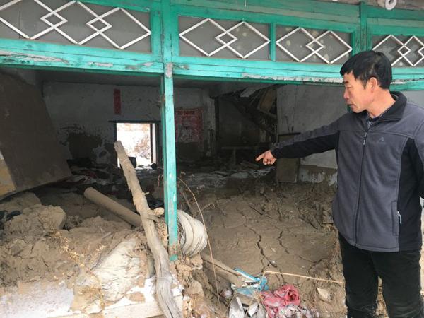 偏岭镇丰富村第二居民组村民鞠忠诚指着一处堆满废弃生活品的房子说,他的媳妇就在这里被泥石流埋没。
