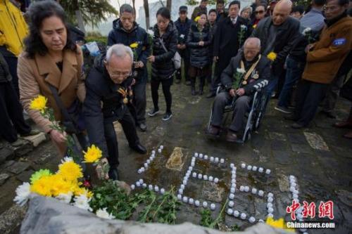 2016年12月12日,在第三个国家公祭日来临之际,参加过1937年南京保卫战的抗战老兵、侵华日军南京大屠杀遇难者家属、南京1213志愿者联合会的志愿者们来到南京光华门遗址公园,向这片曾经发生过激烈战斗的阵地献上和平岁月里的悼念菊花。 中新社记者 泱波 摄