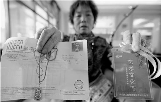 """吴宝园向记者展示在澳门所购的""""金镶玉""""挂件及相关票据。"""