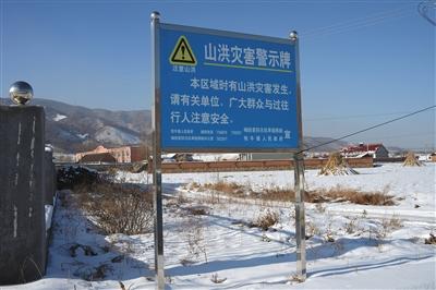 """12月14日,一块""""山水灾祸警示牌""""耸立在南马峪村。"""