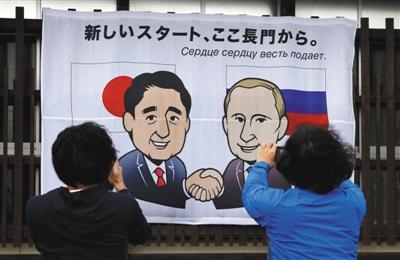 12月14日,日本长门市,民众在印有日本首相安倍晋三和俄罗斯总统普京卡通肖像的横幅前拍照。安倍晋三将于15日与来访的普京会谈。 图/视觉中国