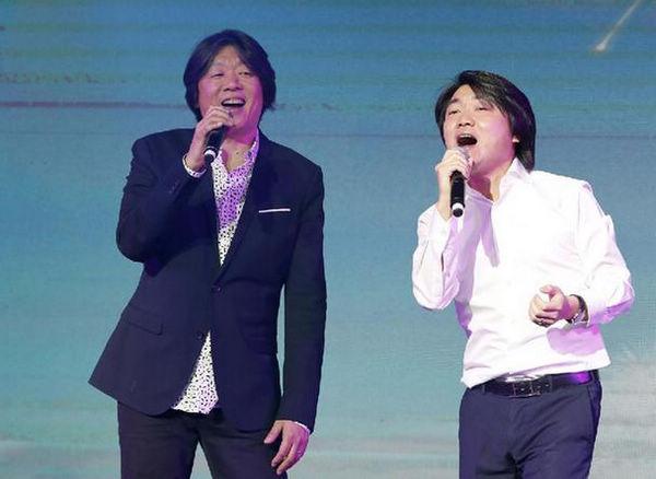 著名歌手老狼(左)与小鬼当佳/美时美刻摄影集团创始人、董事长宋涛在颁奖仪式上演唱