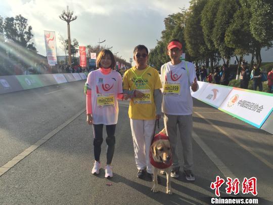 图为彭斌、胖虎及自愿者在上合昆明国际马拉松赛场 陈静 摄