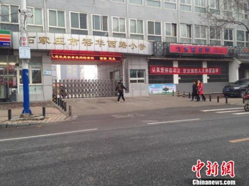 21日下午,一名行人从石家庄市一所小学门前经过。当天,该市小学、幼儿园因重霾停课。 王天译 摄