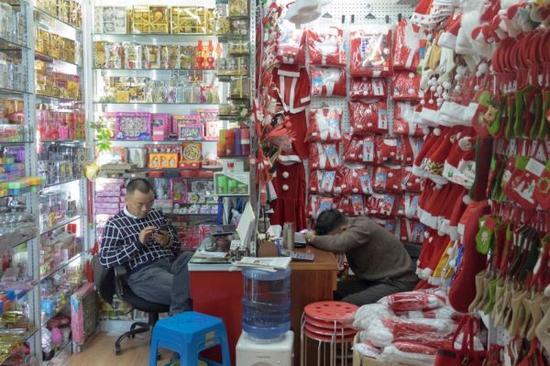 """义乌全年销售圣诞老人和LED发光驯鹿,这里几乎每天都过圣诞节。年复一年,连续数月义乌圣诞村马力全开投入生产。还在盛夏的时候,工人们就开始注塑、缝边和喷漆。但是""""义乌圣诞村""""并不是为本地市场服务的。"""