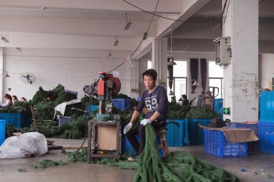 一名工人在制作塑料圣诞树。
