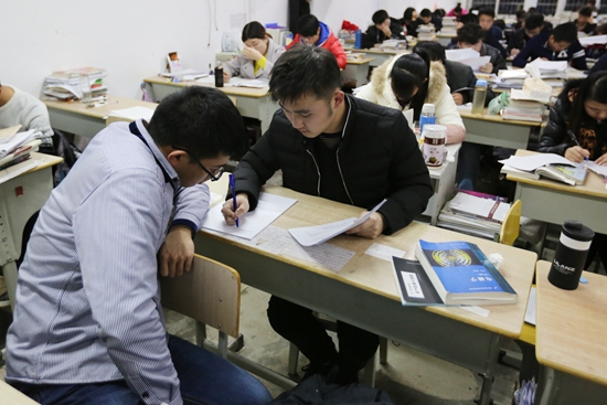 12月20日,安徽安庆,两名考研学生在讨论�y靴之上�y光�W�q问题。 视觉中国 图