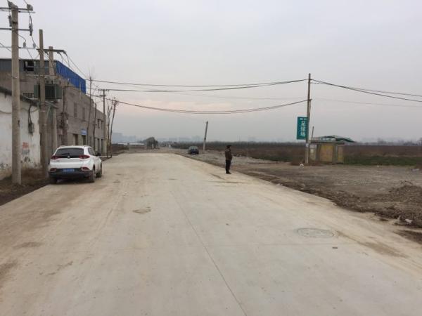 这条村道左侧为34户村民住宅,右侧通过一条百米开外为查丁的足球场 澎湃新闻记者王健 图
