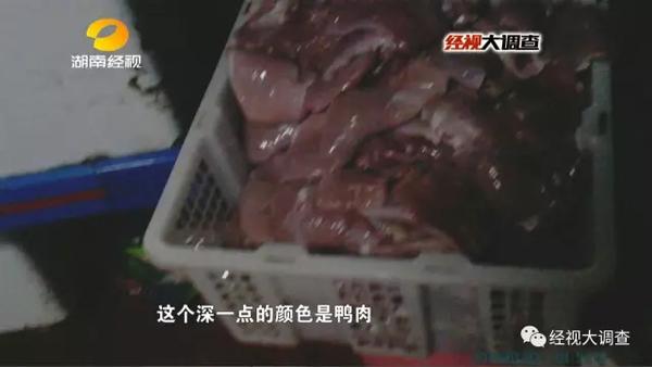 一位工人把去皮鸭大胸放入绞肉机中,把鸭肉打碎,掉到地上的鸭肉又被捡起来重新利用。