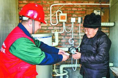 近日,在通州区潞城镇崔家楼村,国网北京电力的工作人员正在向今年装上空气源热泵的村民介绍使用方法和维护人员的联系方式。 本报记者 邓伟摄