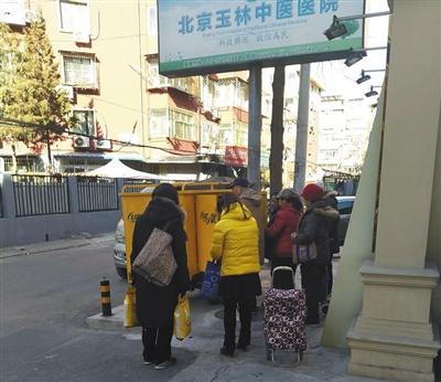 昨日,北京玉林中医院门口,买完药的患者领取礼品。