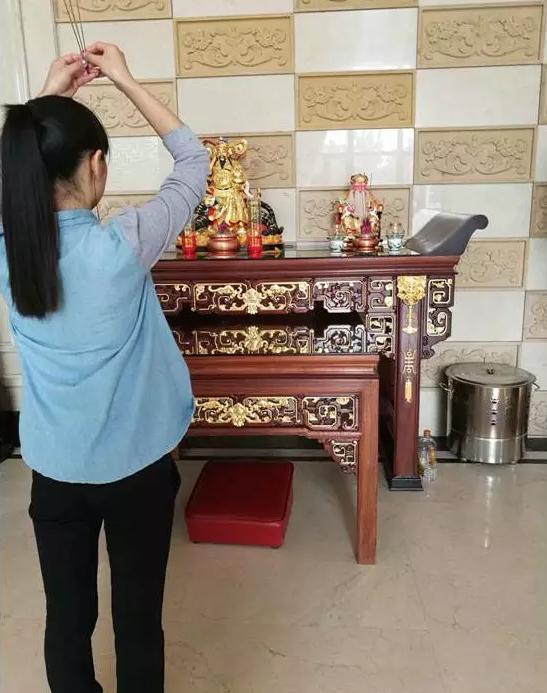 前台坐在靠近电梯一侧的金黄色的办公桌上,近中午1点,她起身给财神爷和寿星鞠躬上香,插上香炉之后再次鞠躬。