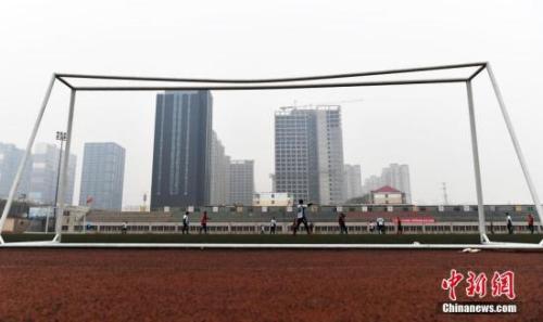 资料图:2016年12月25日,河北石家庄一大学内的体育场上,一群足球爱好者正在霾中踢足球。当日,河北省气象台继续发布霾黄色预警。 中新社记者 翟羽佳 摄