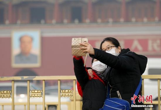 材料图:12月21日,北京延续雾霾,氛围重度净化。图为旅客在天安门广场观光。中新社记者 杜洋 摄