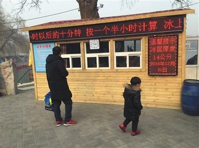 昨日,一对父子来到陶然亭公园冰场售票处,该冰场尚未开放。 本版摄影/新京报记者 信娜