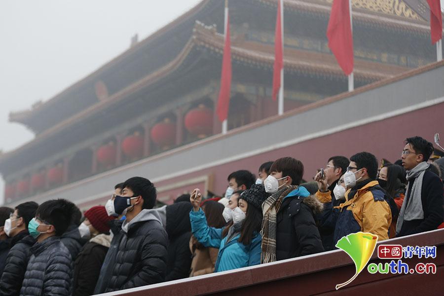现场观礼群众用手机记录下国旗缓缓升起的场景。 中国青年网记者 李拓 摄