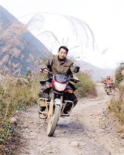 庞家奎骑摩托去新学校给学生上课。 本版图/记者 罗伟