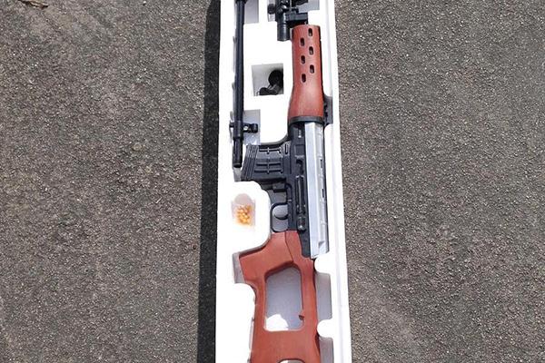 """在一支包装已打开的""""穿越火线SVD模型枪""""盒子内,还配有一包黄色""""BB弹""""。"""