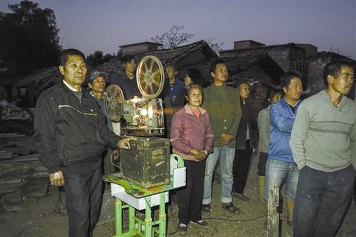 天亮了,罗衍宗(左)在露天放影戏给乡民看。