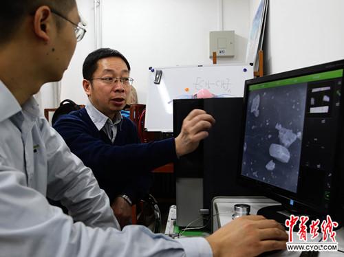 1月3日,北京化工大学高分子纳米复合材料实验室,副教授、博士生导师刘勇(左二)和工作人员一起操作台式扫描电子显微镜,观看微米级的雾霾颗粒。中国青年报・中青在线记者 陈剑/摄