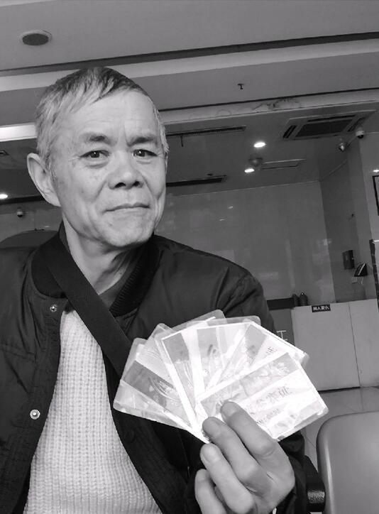 老人手中展示的是历年参加横渡钱塘江活动的参赛证。
