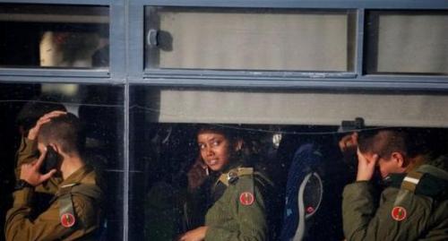 事故发生后,其他士兵坐在大巴车上等候离开事件现场。