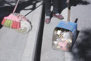 环卫工人清扫车主丢弃的广告卡片