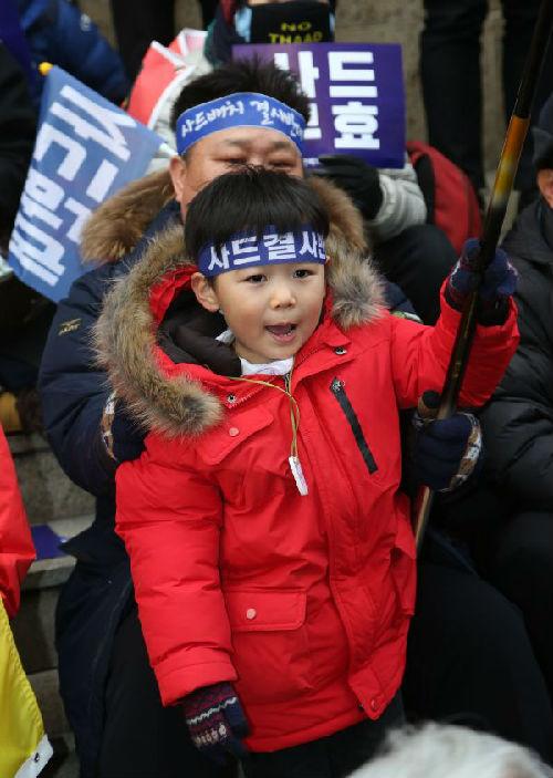 """韩国民众集会反对部署""""萨德""""系统。新华社发"""