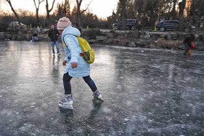 昨日,清华大学内,学生落水荷塘附近另一冰面上,仍有人滑冰。