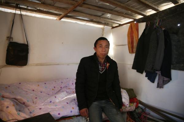 41岁的工人石纪斌在四处透风的工棚内住着,希望今年不要空手回家。澎湃新闻记者 谢匡时 图