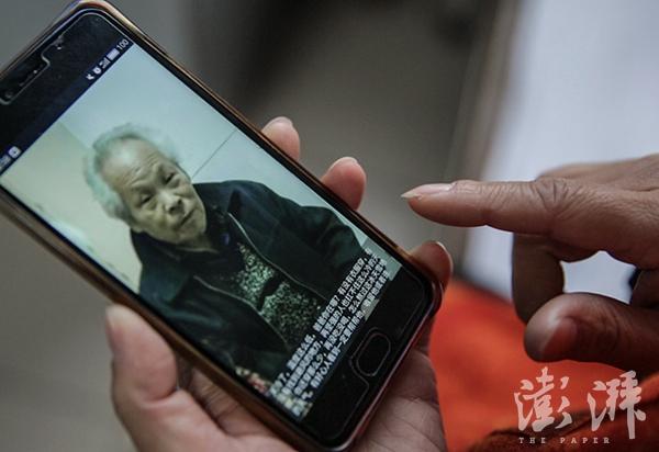 宋珍明看着手机里父亲的照片。