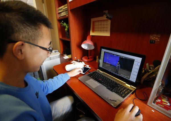 资料图片:学生在家中通过网络教室在线听课 新华社发(周良 摄)