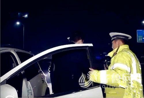 白色轿车司机下车接受交警夜查