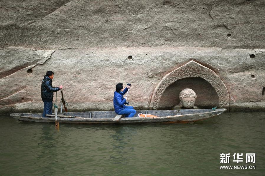 (3)考古人员在对露出水面的佛头进行拍摄(1月8日摄)。