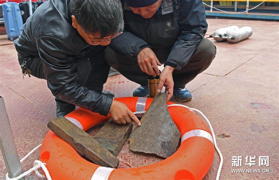 (7)考古人员在观察打捞上来的物品(1月8日摄)。