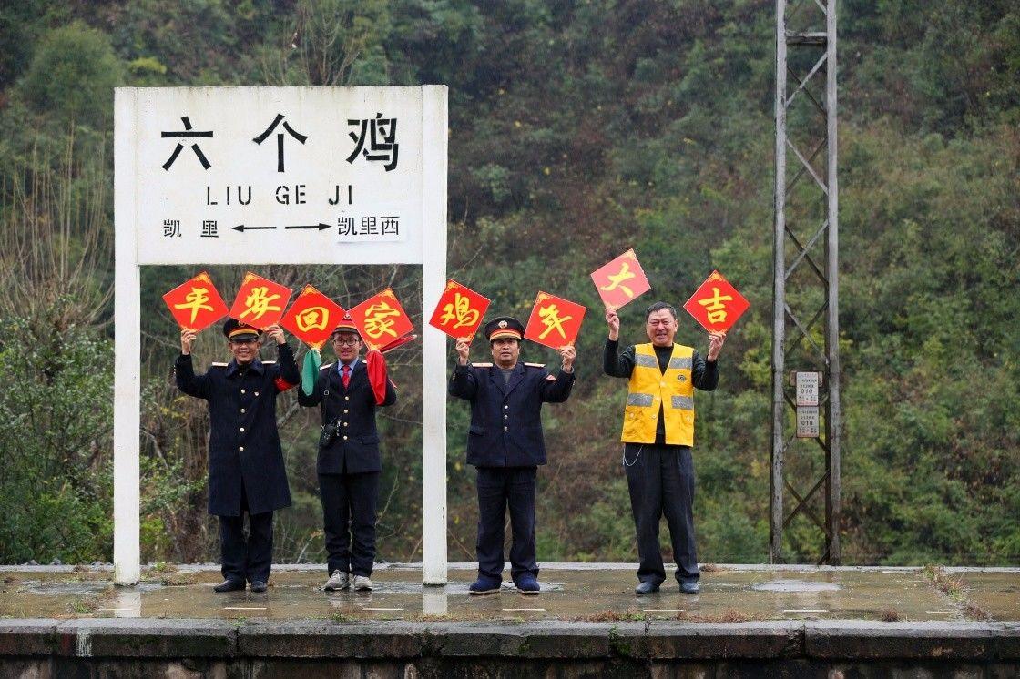 """2017年春运大幕即将开启,1月12日,在贵州凯里境内沪昆铁路六个鸡火车站,站长汪祁斌(左一),职工甘功灵(左二)、雷忠(左三)、李春生(左四)为即将到来的2017年春运送上""""平安回家、鸡年大吉""""的祝福。2017年春运将从1月13日开始至2月21日结束,共计40天。新华社发(吴吉斌 摄)"""
