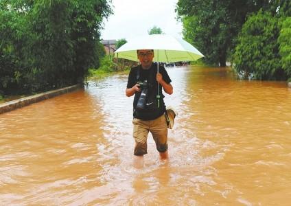 张磊在大水中采访。材料图像