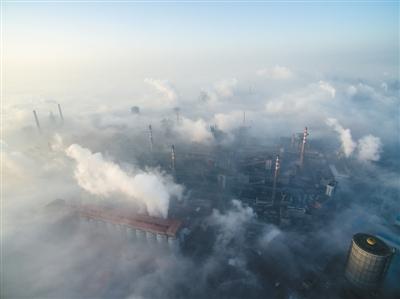 2016年12月22日,邯郸,钢铁厂烟囱穿过晨雾。 新京报记者 王子诚 摄