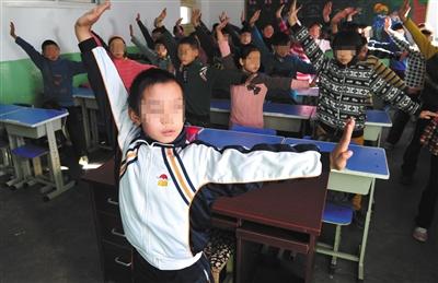 """2013年12月11日,石家庄某小学学生在教室内演示""""防霾""""武术健身操。图/视觉中国"""