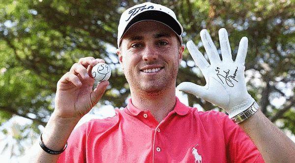 贾斯丁-托马斯赛后展示印有59杆字样的球和签名手套