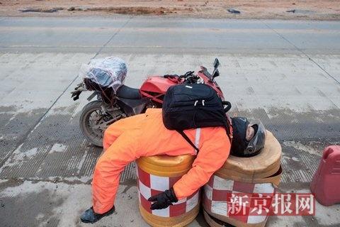1月16日下午,在柳州境内,骑行16个小时的牟安虎疲惫不堪,躺在路边隔离桩上休息。