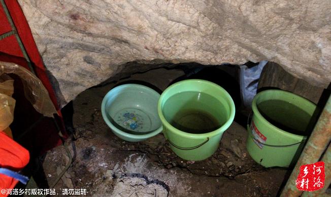 吃水也是个费事事,他的小棚子依靠的岩穴石头往下滴水,他就用桶接了贮存,之前是在洞里住,因为湿润,才搭建了这个粗陋的棚子。